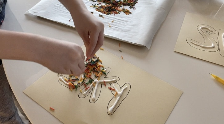 child sprinkling colored spaghetti pieces over the glue in art project