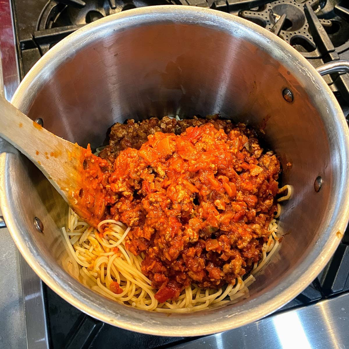 Mixing sauce into pasta in large pot