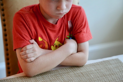 child sitting at table unhappy