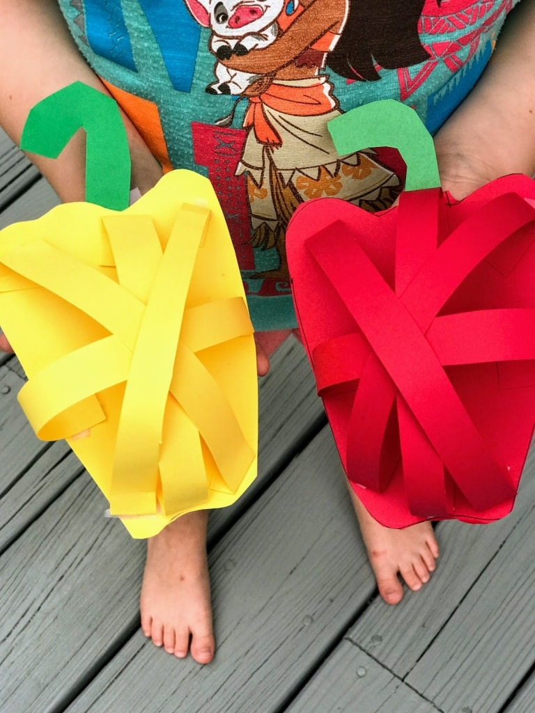 child holding 3d paper craft of bell peppers
