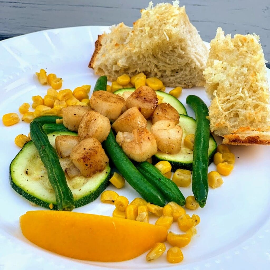 seared scallops over green beans, zucchini and corn on plate