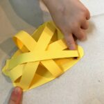 Placing third yellow strip on 3d paper pepper