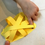 Placing fourth yellow strip on 3d paper craft of bell pepper