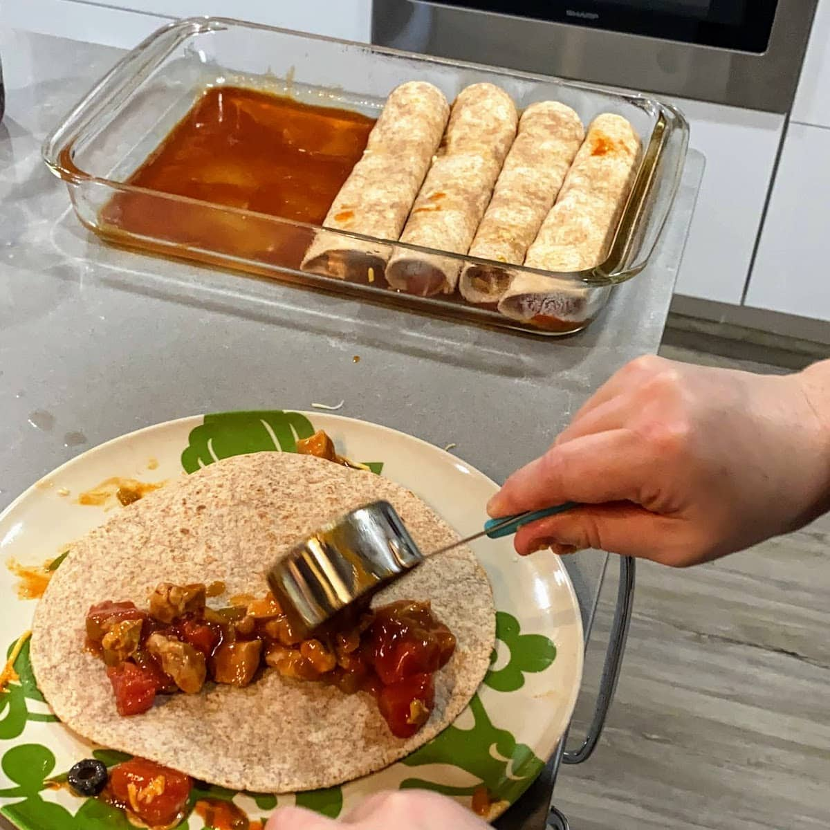 person assembling enchiladas