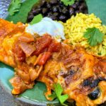 plated chicken enchilada with sour cream, cilantro, beans and rice