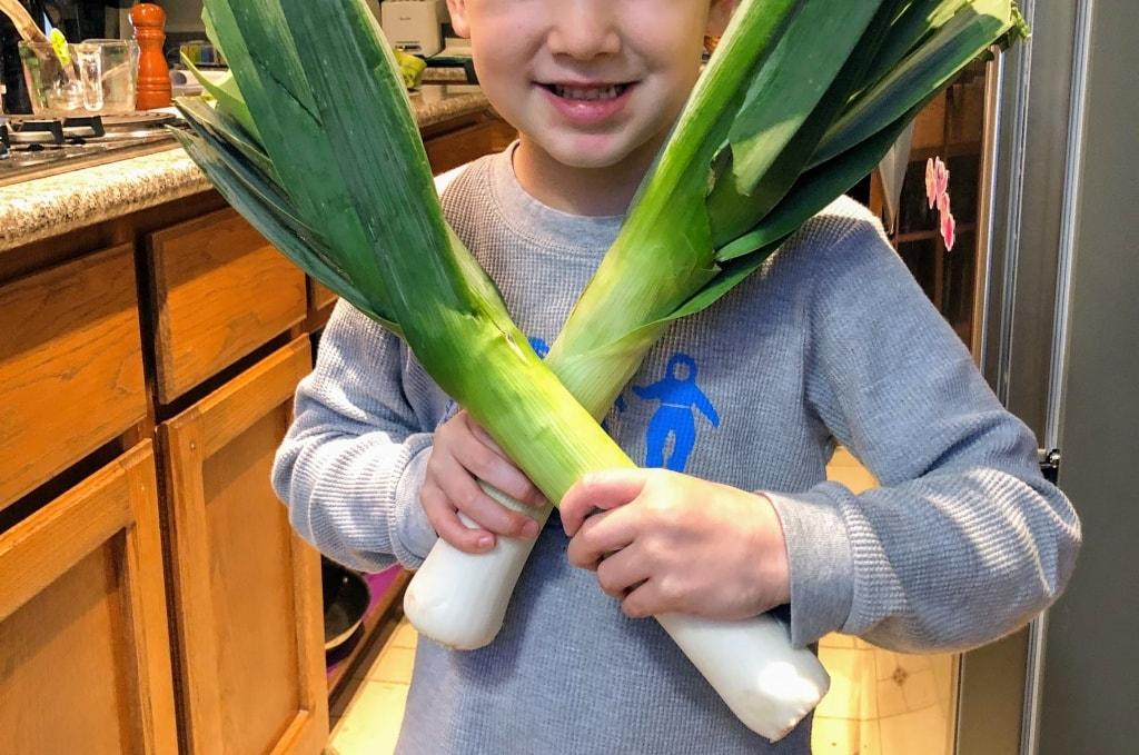 child holding leeks