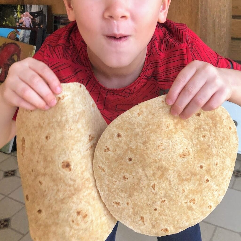Child holding whole wheat tortillas