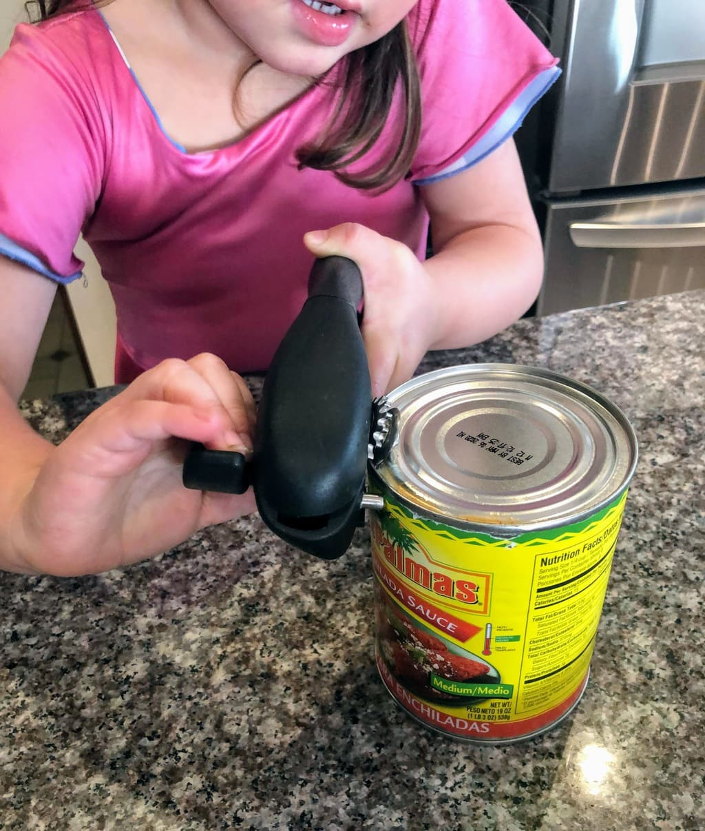 child opening can of enchilada sauce with can opener