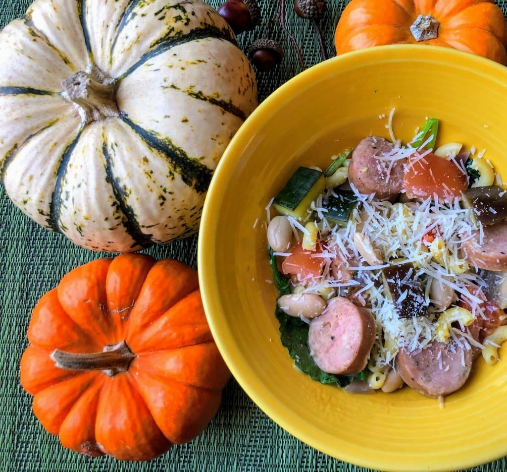bowl of chicken sausage and pasta dish, pumpkins around the bowl