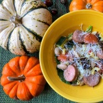 bowl of chicken sausage and pasta dish, pumpkins around the bowl