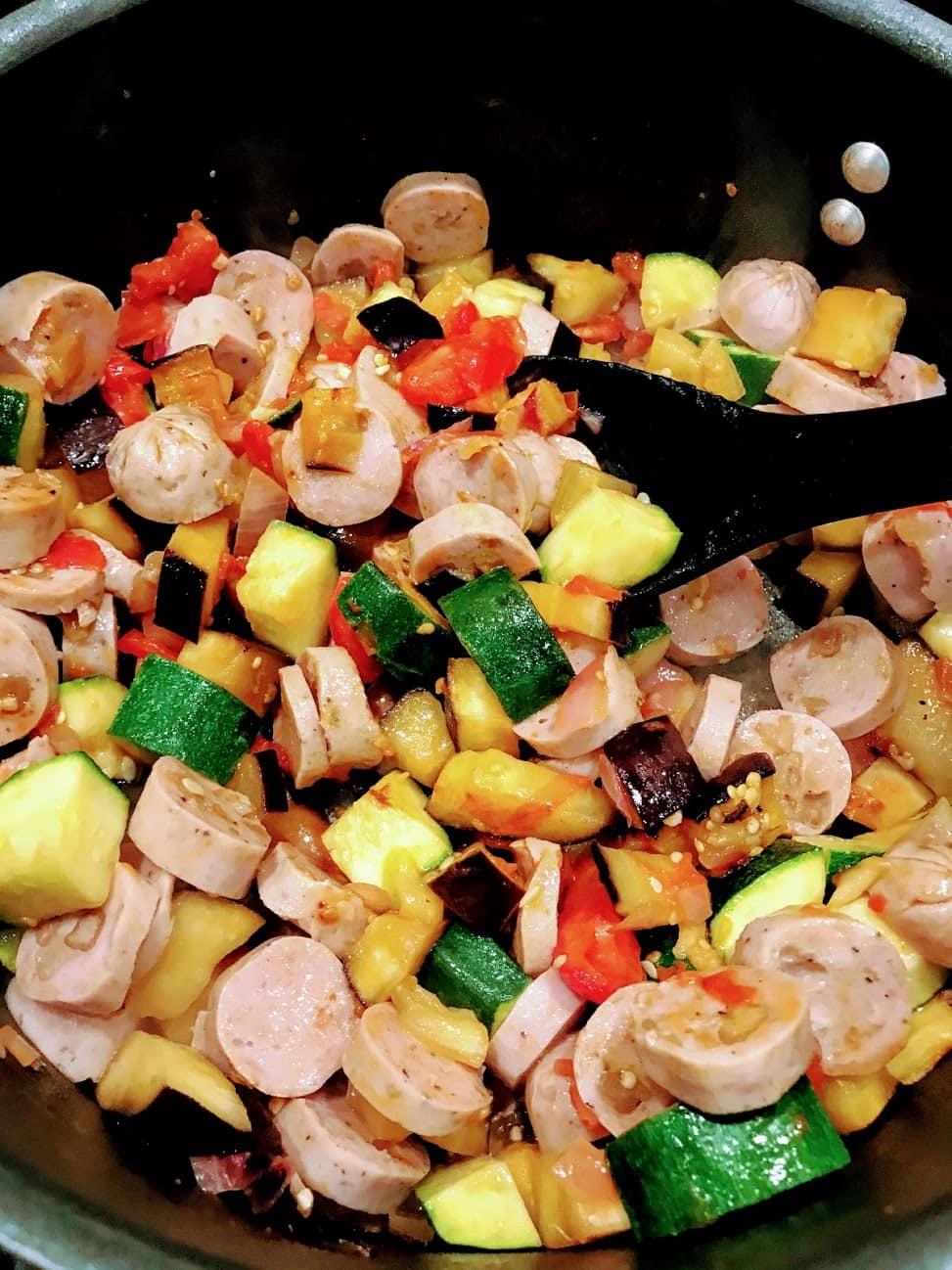 cooking apple sausage and veggies on pan