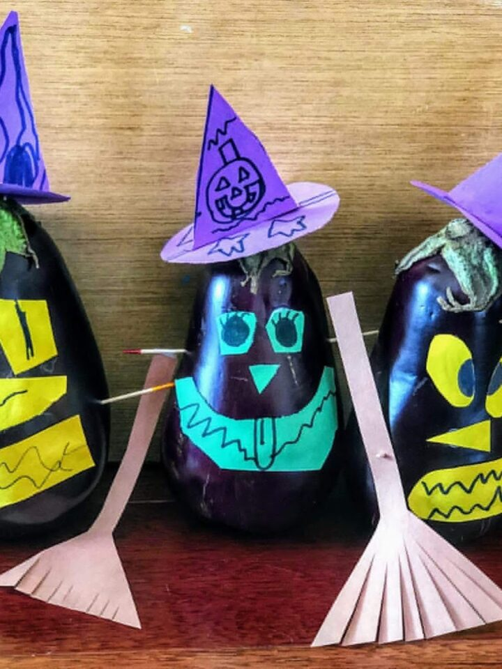 three eggplants decorated as witches with paper: purple hats, bronw booms, and green/yellow spooky faces