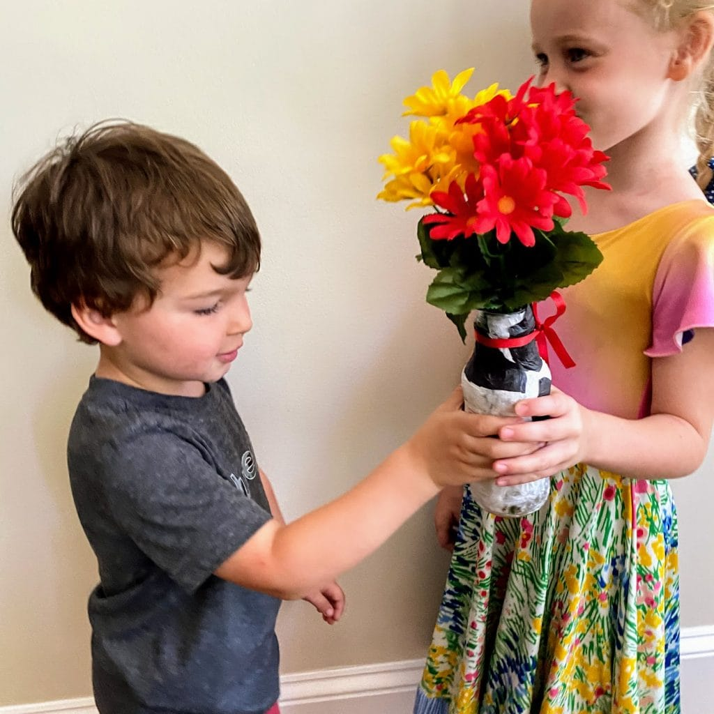 two kids playing with tissue paper vase craft
