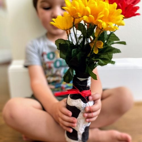 child holding tissue paper vase with flowers