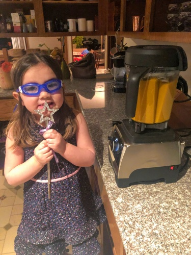 Child standing next to vitamix filled with butternut squash soup