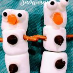 two snowman made from marshmallows and candy