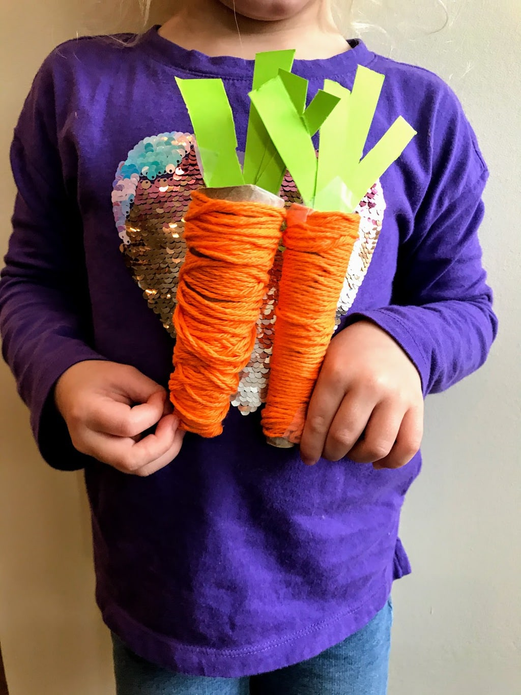 child holding two play food carrots made from orange yarn