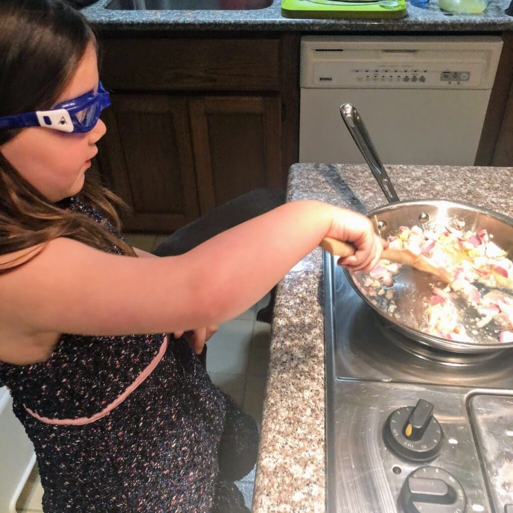 child cooking shallot and garlic in pan