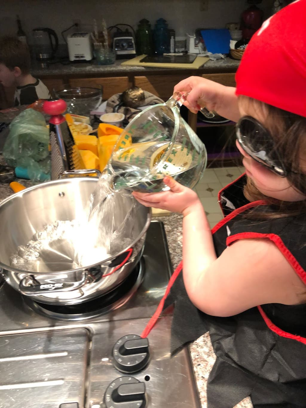 child pouring water into pot