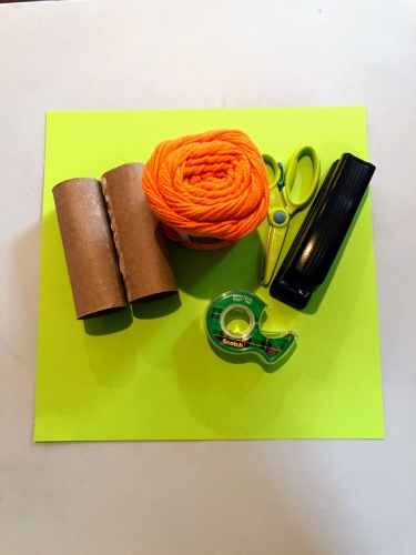 toilet paper rolls, orange yarn, scissors, stapler, tape and green paper