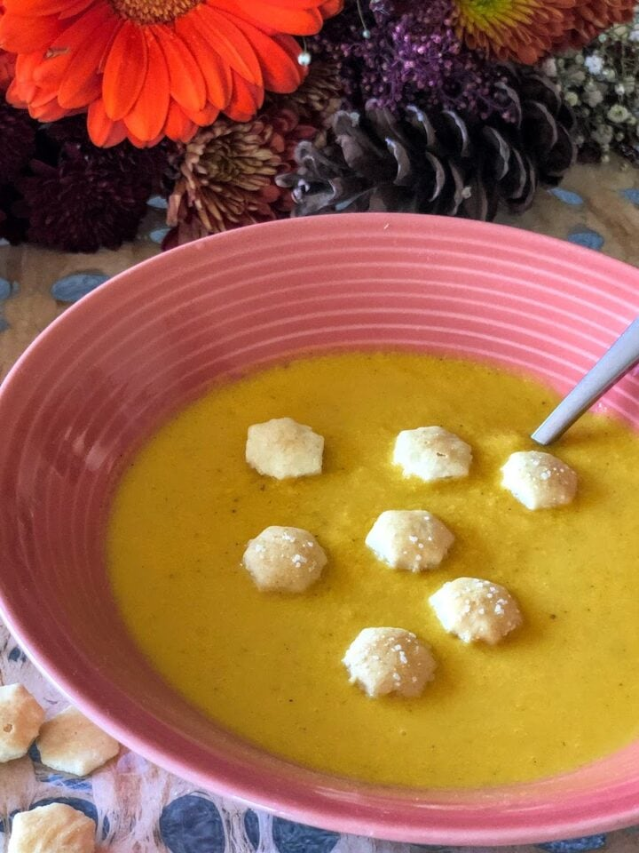 butternut squash soup in bowl topped with small crackers