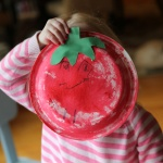 child holding Paper Plate Craft Sponge Art Tomato craft