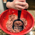 child mixing turkey slider ingredients
