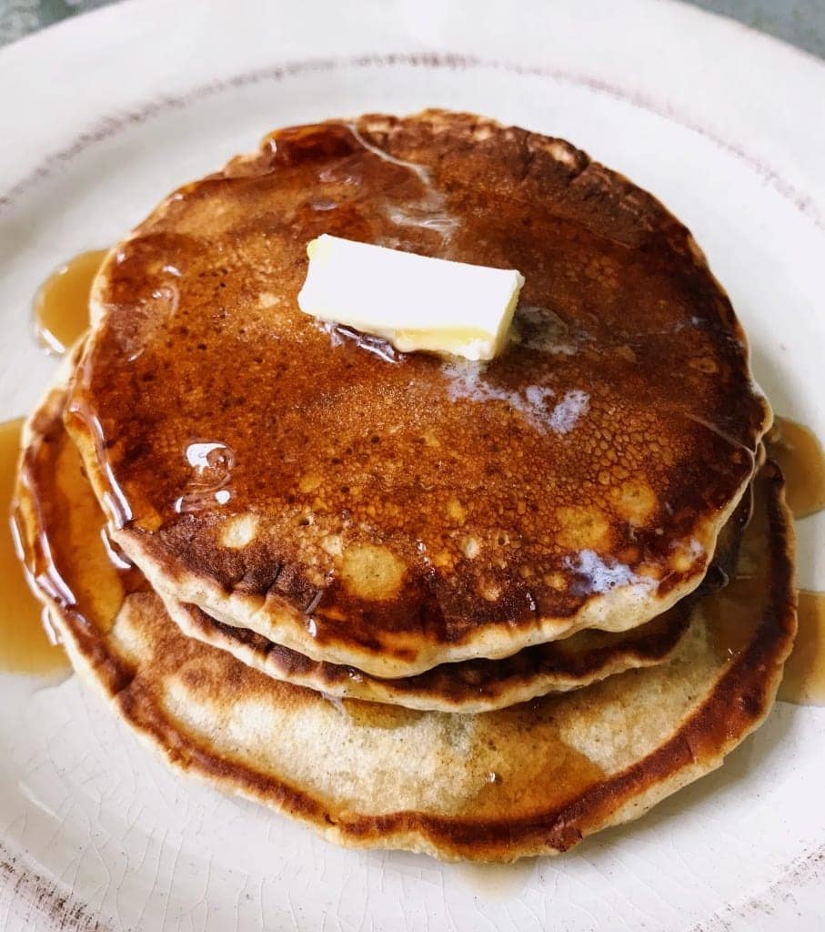 stack of three fluffy pancakes with butter and syrup