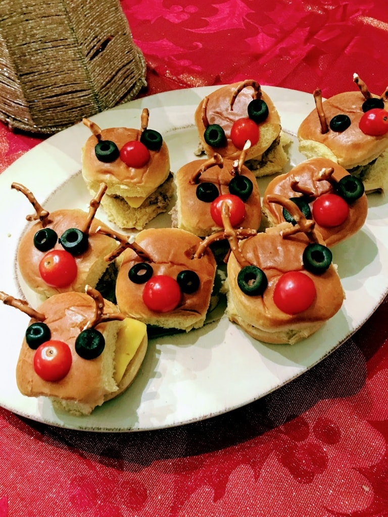 Christmas burgers with reindeer faces made from veggies and pretzels on plate