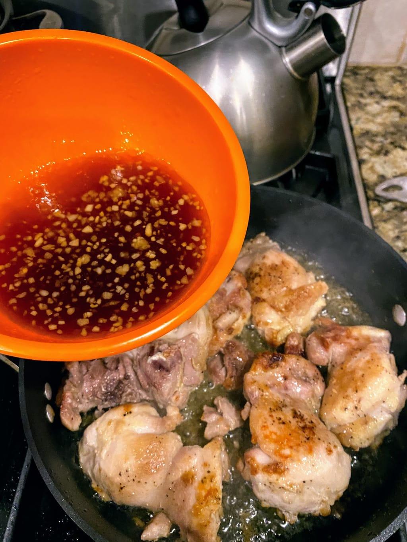 Adding honey garlic sauce to chicken thighs