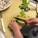 Child cutting celery on manila cutting board, for chicken salad