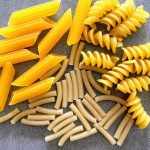 penne, macaroni & rotini on a gray counter