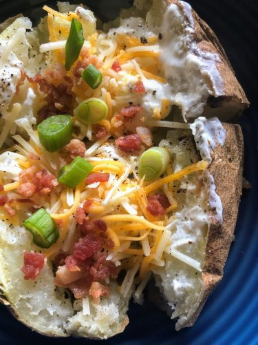 baked potato with scallions, cheese, bacon and sour cream