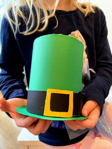 girl holding leprechaun hat