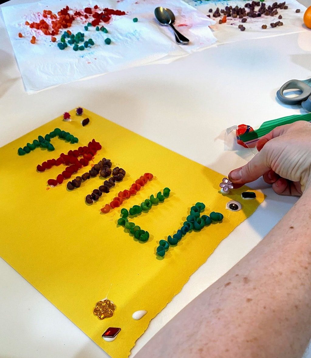 Girls gluing jewels to paper