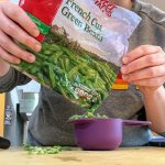 pouring frozen green beans from bag into purple measuring cup