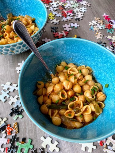 pasta with chickpeas and chives in blue bowl on table with puzzle pieces