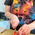 woman with rainbow wolf t-shirt, slicing red bell peppers