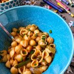 pasta with chickpeas and chives in blue bowl on table with puzzle pieces and crayons
