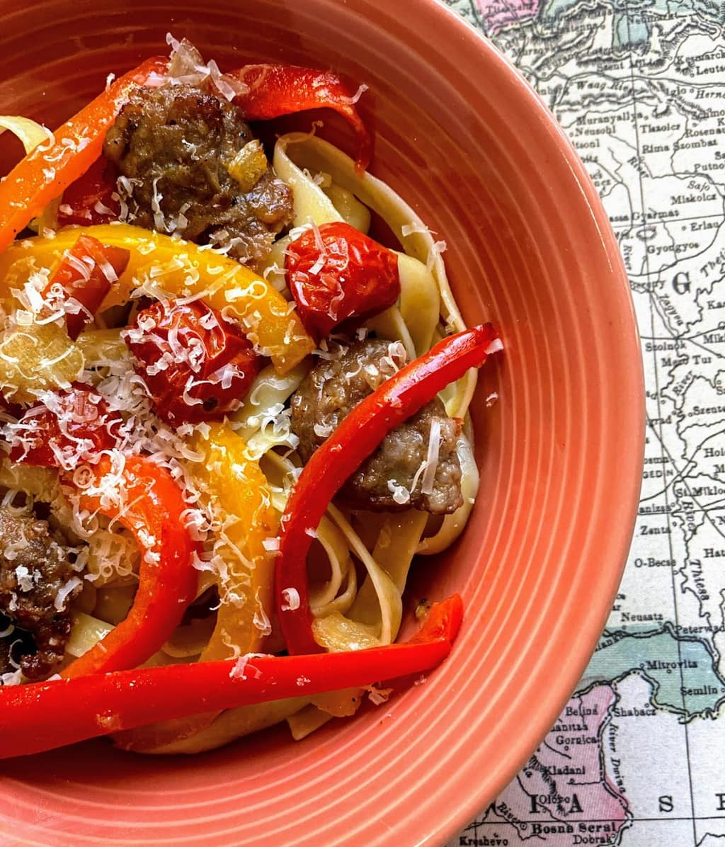 pink bowl on top of world map placemat with oven roasted sausage and veggies over pasta, topped with shredded cheese