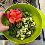 Person adding a cup of watermelon to a big green bowl filled with salad