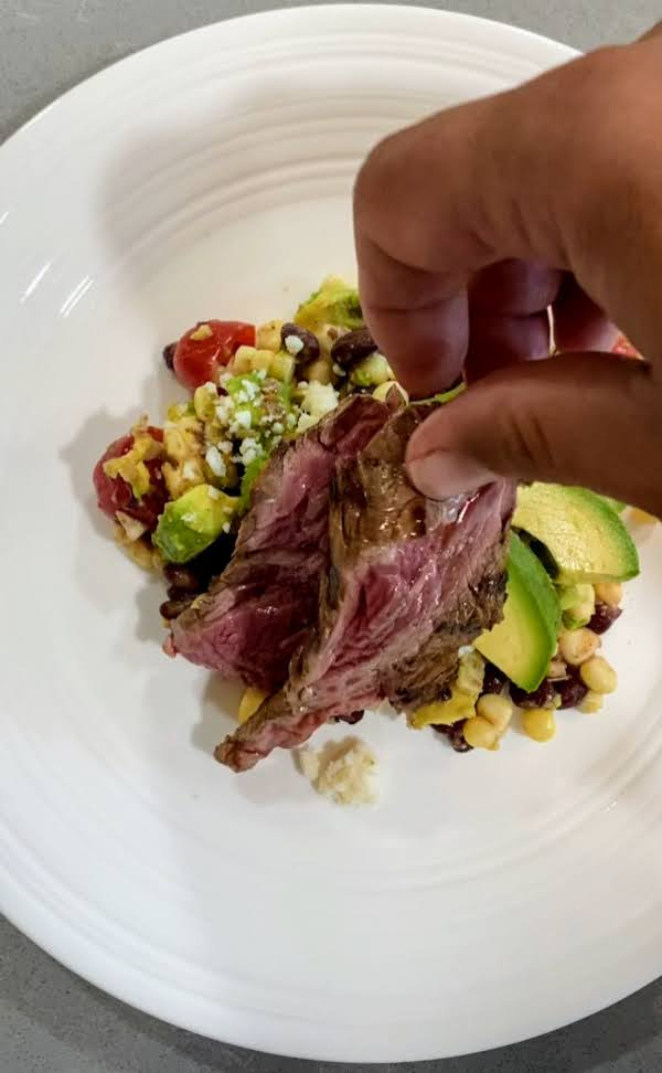 Hand placing steak on white plate with avocado and corn salad