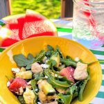 yellow bowl with watermelon salad, ice drink, and slices of watermelon on green and white tray outside