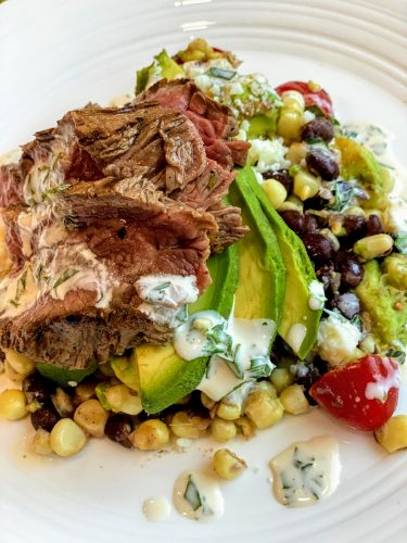 white plate with Carne Asada with Corn Salad and Chimichurri Sauce