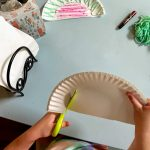child cutting paper plate