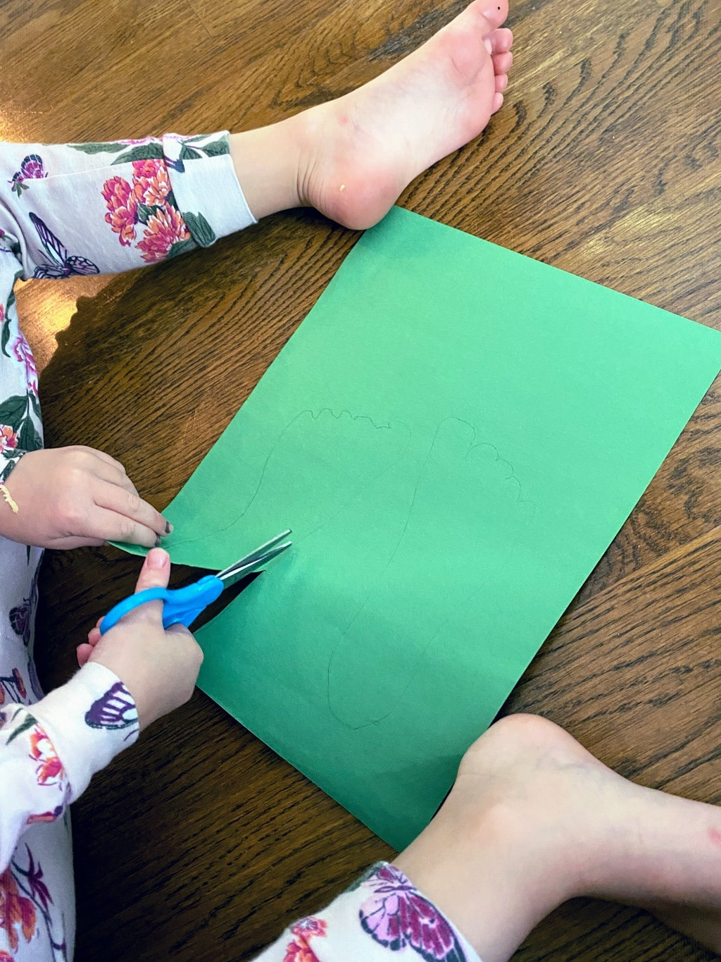 child cutting out footprint