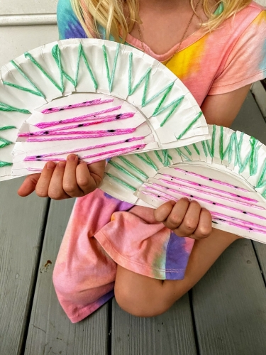 child holding two paper plate watermelon