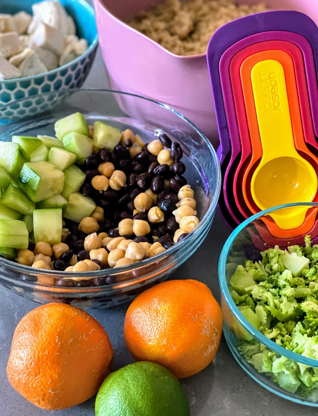 on table: citrus fruit, colorful measuring cups, bowl of chopped broccoli, bowl of chopped cucumber and beans, blue bowl of chicken and pink bowl of cooked quinoa
