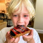blonde boy eating piece of toast that's painted with striped of different colors