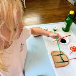 "child painting toast with letter ""H"""
